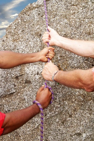 Hände halten gemeinsam ein Seil.