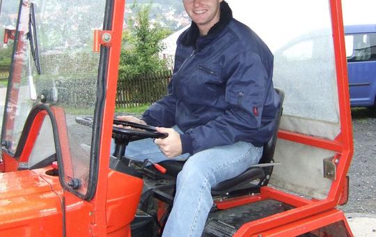 Ein junger Mann sitzt auf einem roten Traktor.