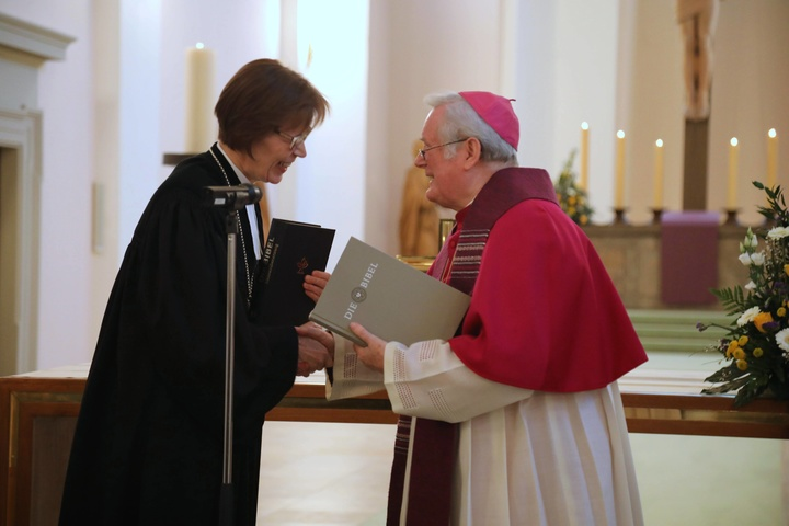 Bischof Friedhelm Hofmann und Regionalbischöfin Gisela Bornowski überreichen sich gegenseitig eine Ausgabe der Einheitsübersetzung beziehungsweise der Lutherbibel.