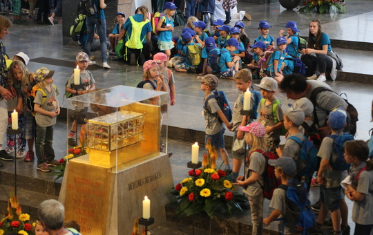 Kinder stehen zur Kilianiwallfahrt um den Schrein mit den Häuptern der Frankenapostel.
