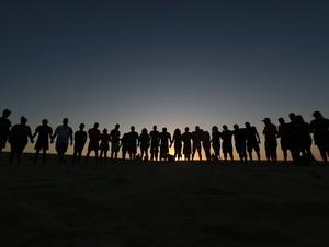 Im Kreis stehende Jugendliche halten zusammen.