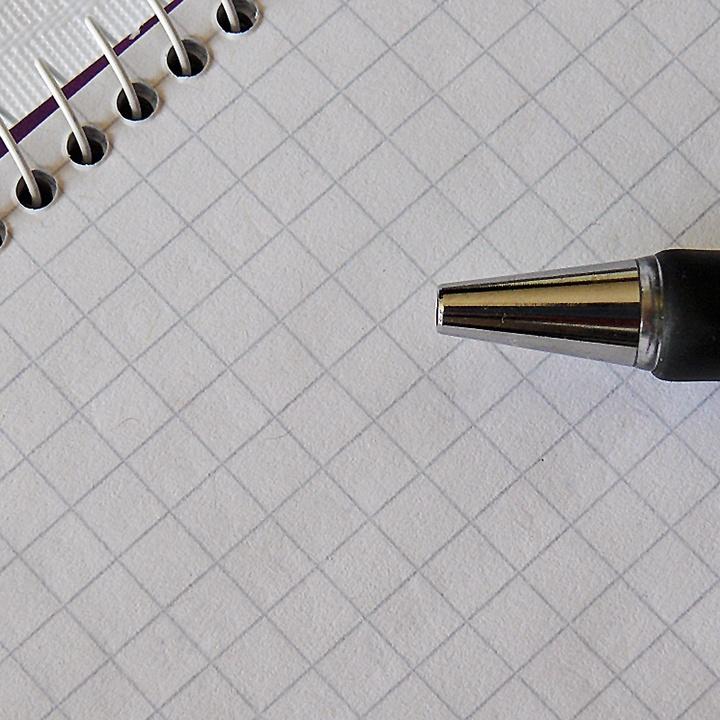 Ein schwarzer Stift liegt auf einem karierten Papierblock