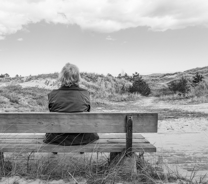 Ältere Dame sitzt allein auf einer Bank