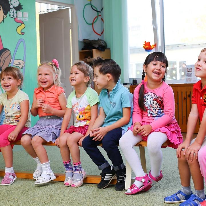 Kindergartenkinder sitzen im Stuhlkreis und lachen.
