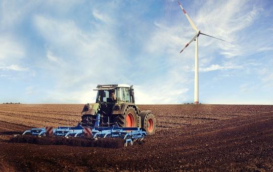 Traktor auf einem Feld mit Windrad