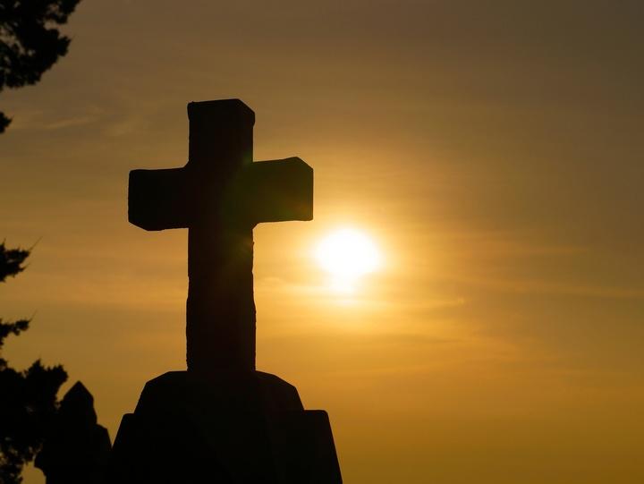 Steinkreuz und im Hintergrund ein Sonnenuntergang