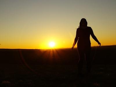 Frau schaut auf untergehende Sonne