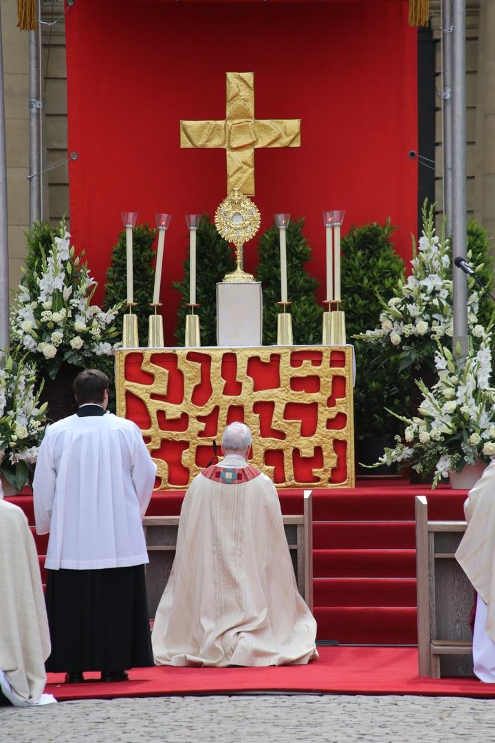 Bischof Friedhelm kniet zu Fronleichnam vor der Monstranz.