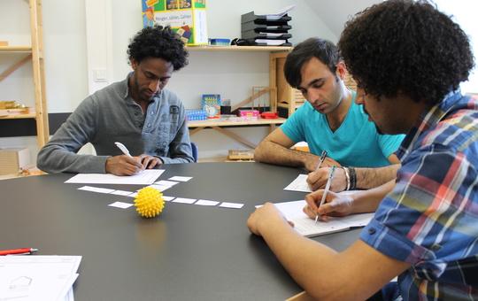 Flüchtlinge lernen zusammen an einem Tisch.