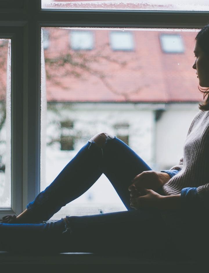 Eine Frau sitzt auf der Fensterbank und schaut hinaus.