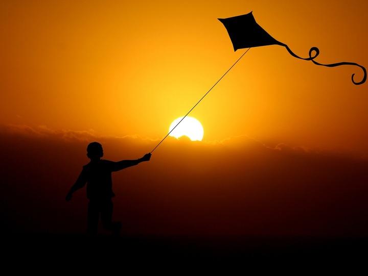 Ein Kind rennt mit einem fliegenden Drachen in den Sonnenuntergang