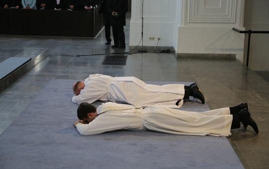 Zwei angehende Priester liegen bei ihrer Weihe auf dem Boden.