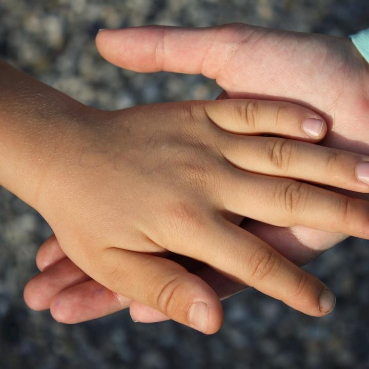 Zwei Hände liegen ineinander.